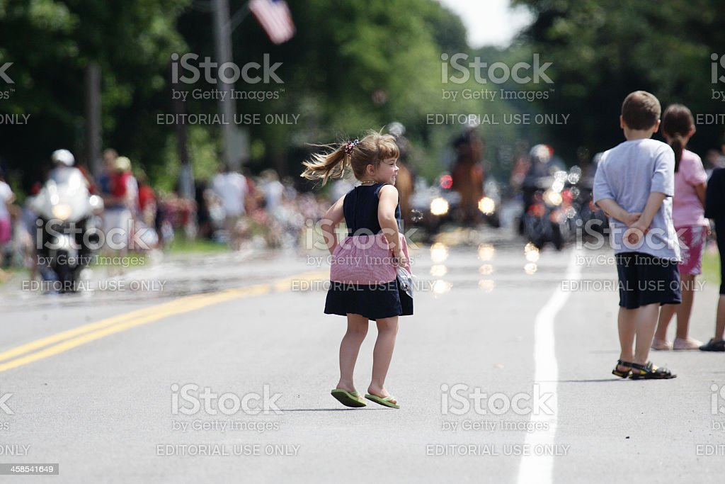 Young Girl Jumping for Joy at the July 4th Parade stock photo
