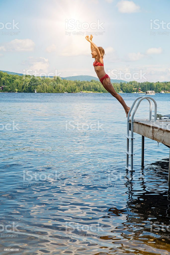 Young girl jumping in lake from pier on sunny day. stock photo