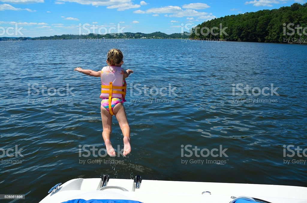 Young girl jumping into lake water stock photo