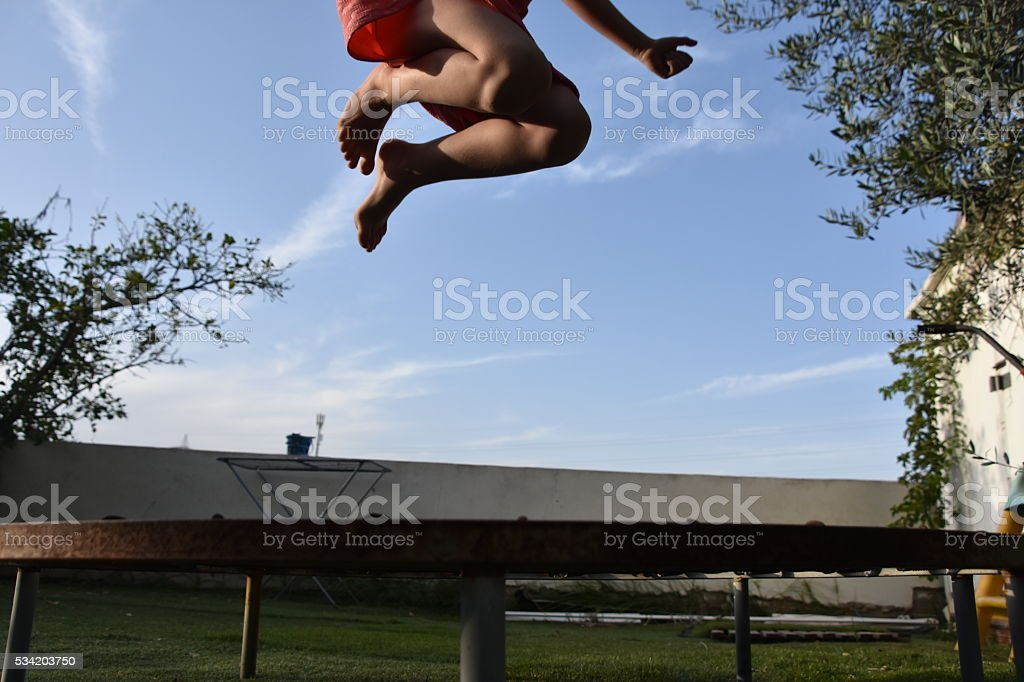 Young girl jumping on a trampoline stock photo