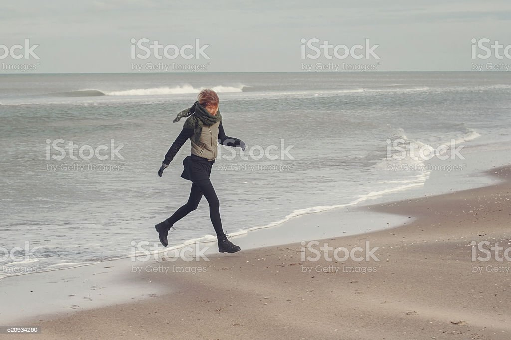 Young girl jumps on the seashore. stock photo