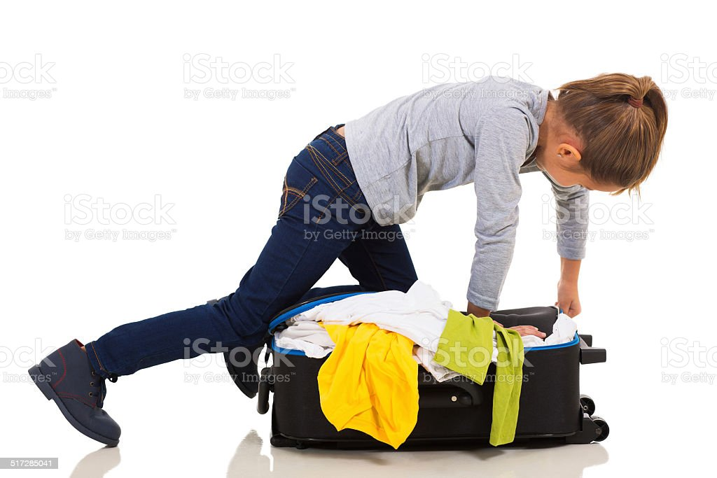 young girl kneeing on suitcase trying to zip it up stock photo