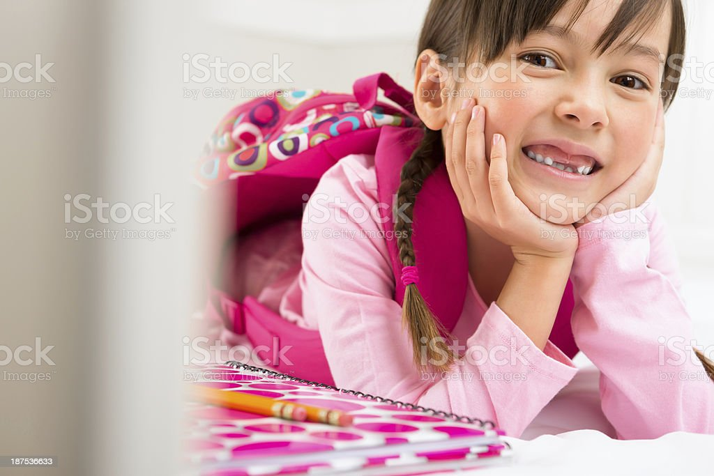 Young girl laying in bed about to do homework royalty-free stock photo