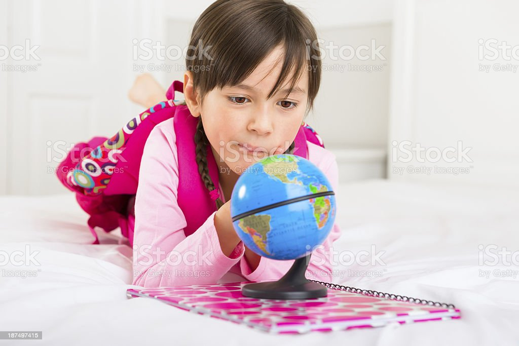 Young girl laying on her bed, looking at the globe royalty-free stock photo