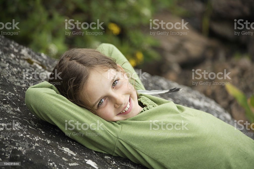 Young Girl Leaning Against a Rock stock photo