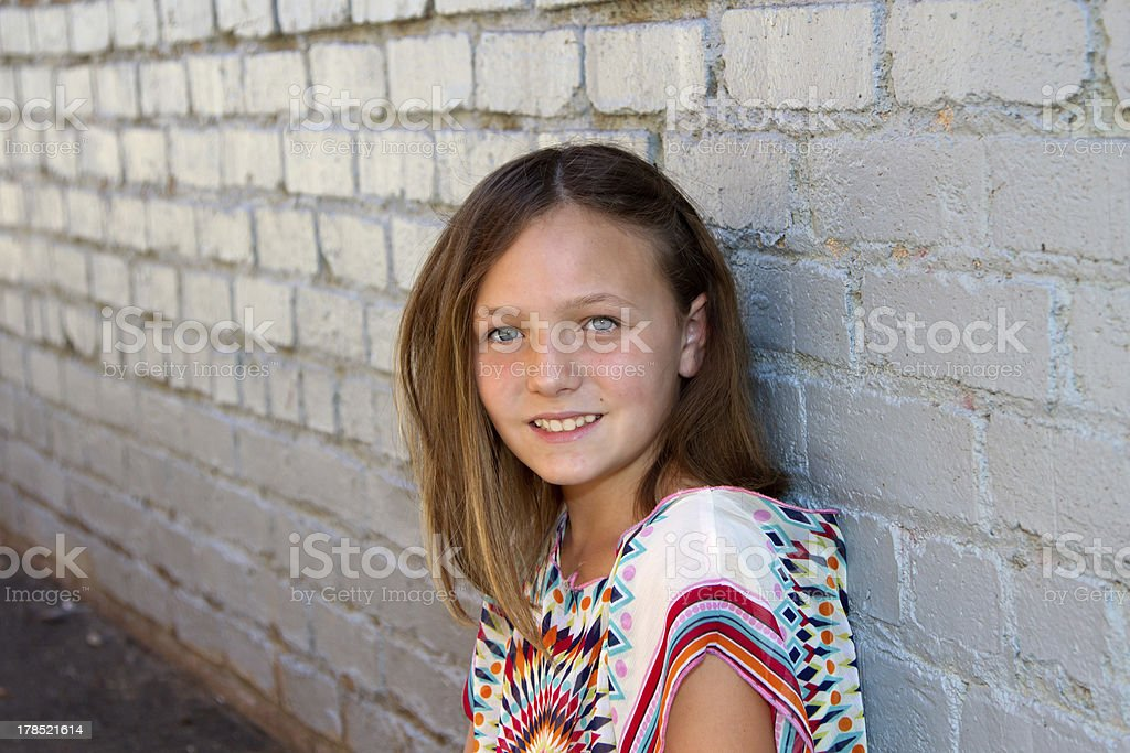 Young Girl Leaning Against A White Brick Wall royalty-free stock photo