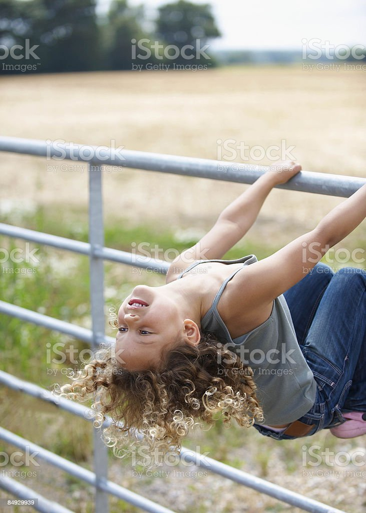 Young girl leaning back on farm gate royalty-free stock photo