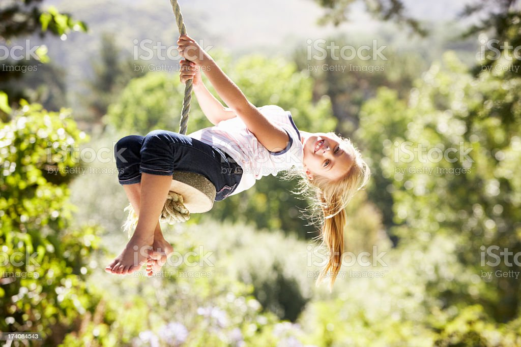 Young girl leaning back on rope swing in sunshine royalty-free stock photo