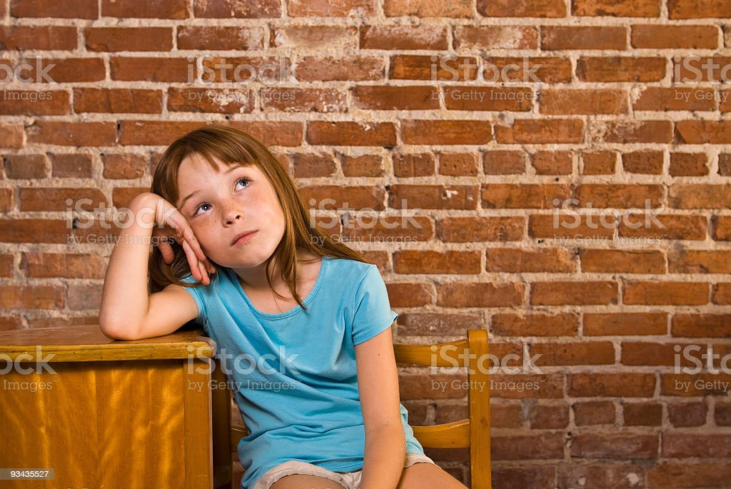 Young girl leaning on school desk thinking royalty-free stock photo