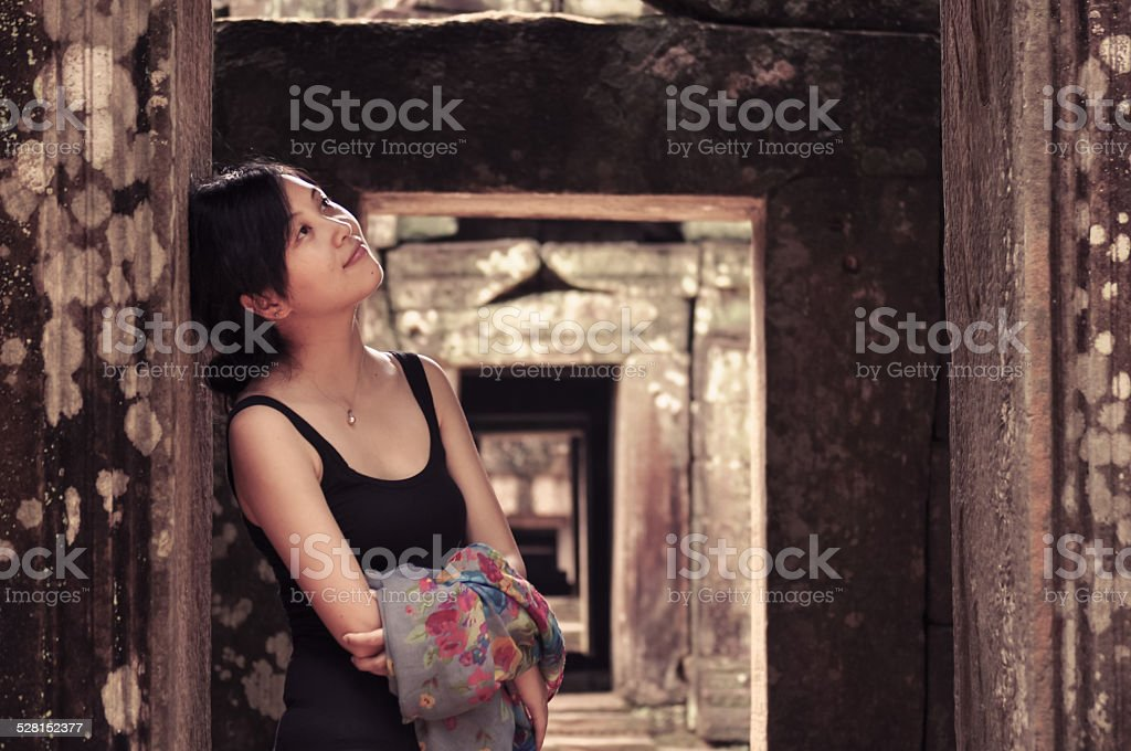Young girl leans on ancient pillar at doorway royalty-free stock photo