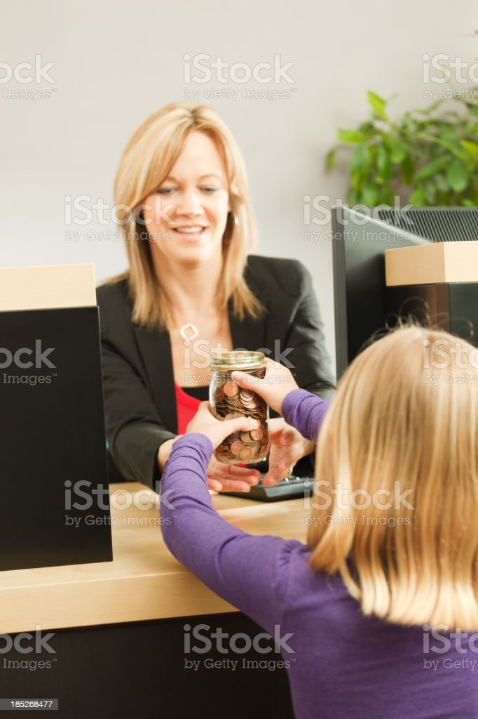 Young Girl Learning about Saving Taking money to Bank Teller royalty-free stock photo