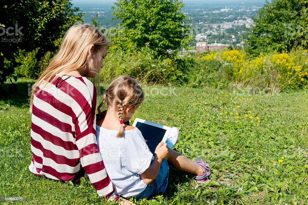 Young girl learning technology with a teenager girl stock photo