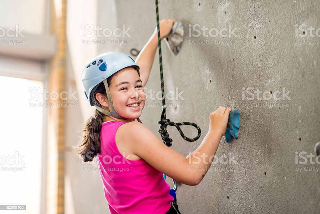 Young Girl Learning to Rock Climb stock photo