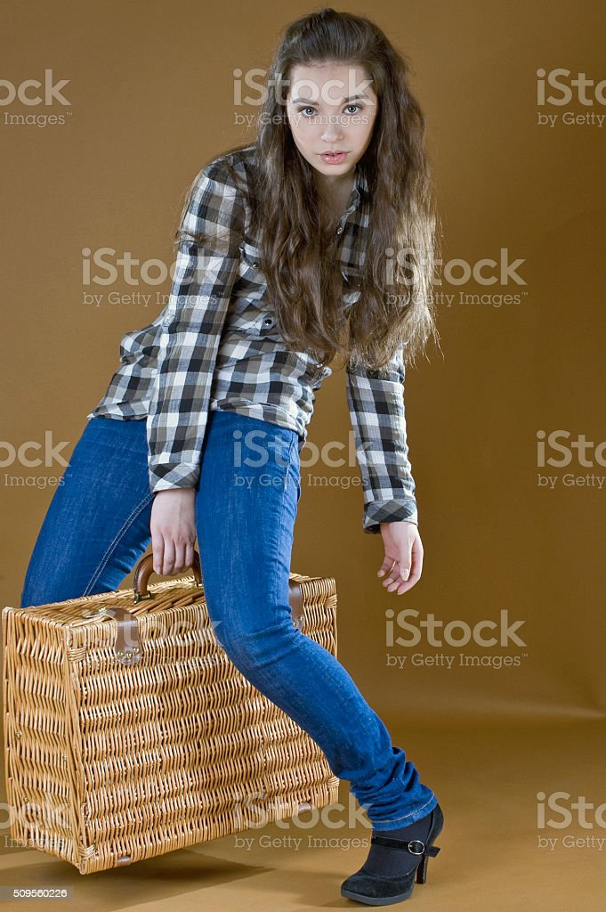 Young girl lifts a heavy woven bag stock photo