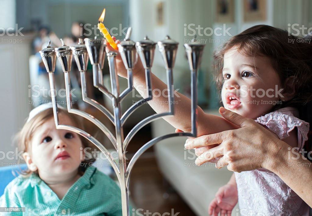Young girl lights the Hanukkah menorah with help from adult stock photo