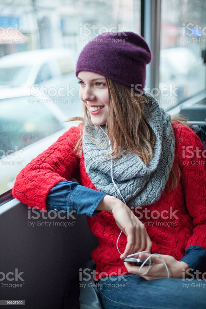 Young girl listening to music on public transport stock photo