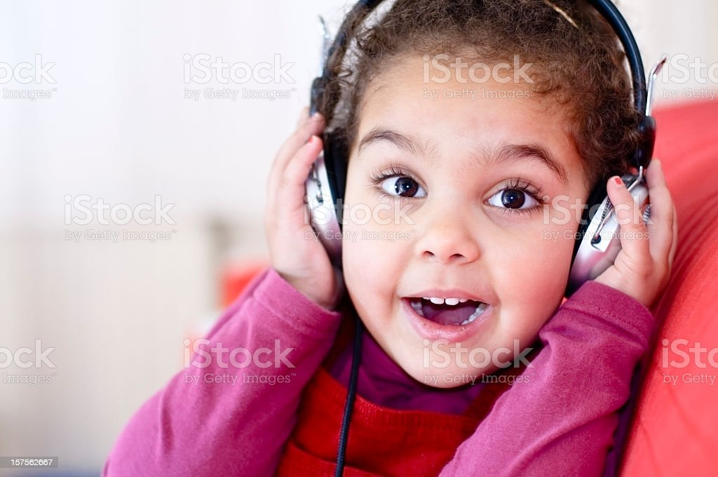 A young girl listening to music with headphones stock photo