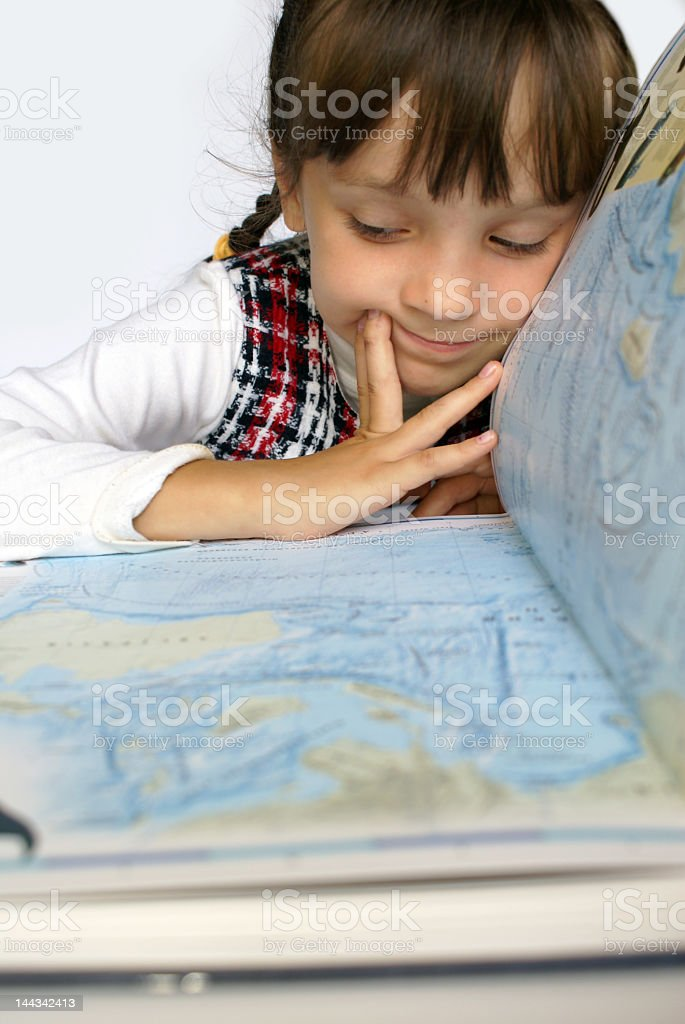 Young girl looking at atlas of maps royalty-free stock photo