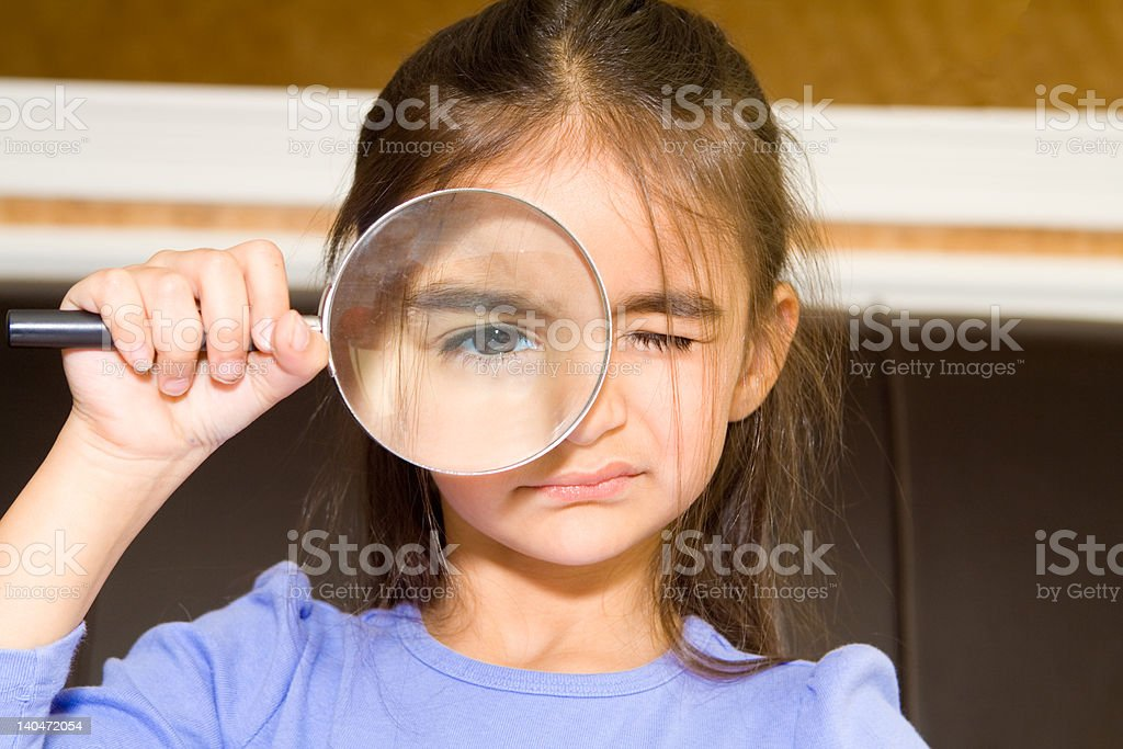 Young Girl Looking at Camera Through Magnifying Glass royalty-free stock photo