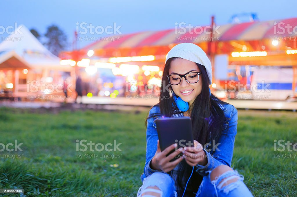 Young girl looking at digital tablet by night in funfair stock photo