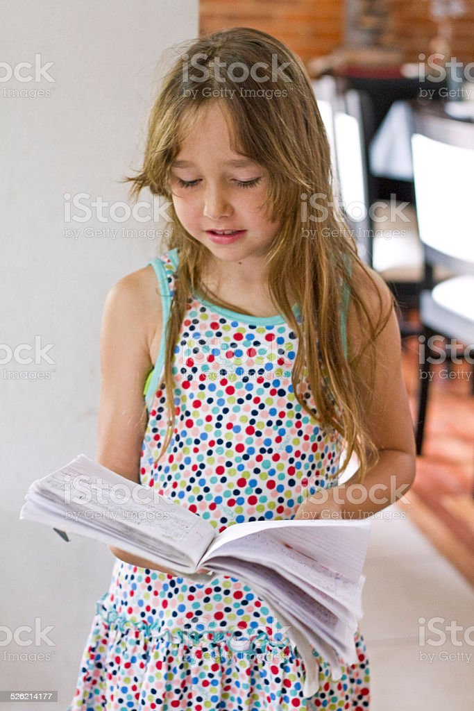 Young girl looking at her book stock photo