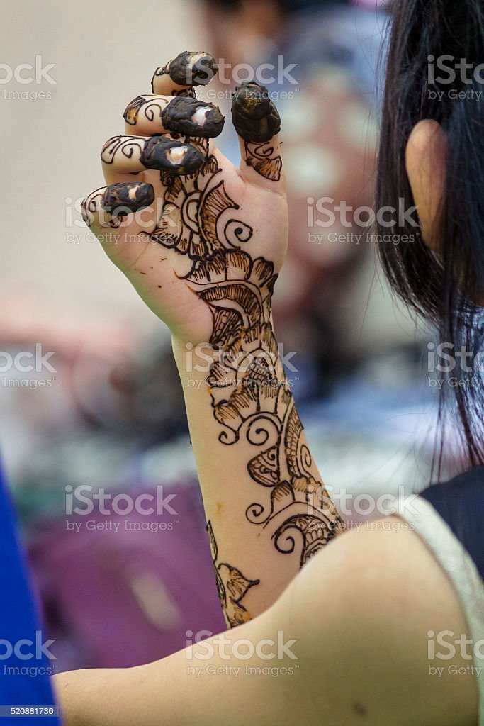 Young girl looking at her heena tatto hand. stock photo
