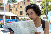 Young girl looking at street map, blurred background