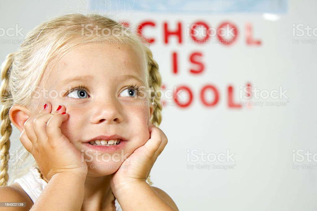 Young girl  looking at teacher in school stock photo