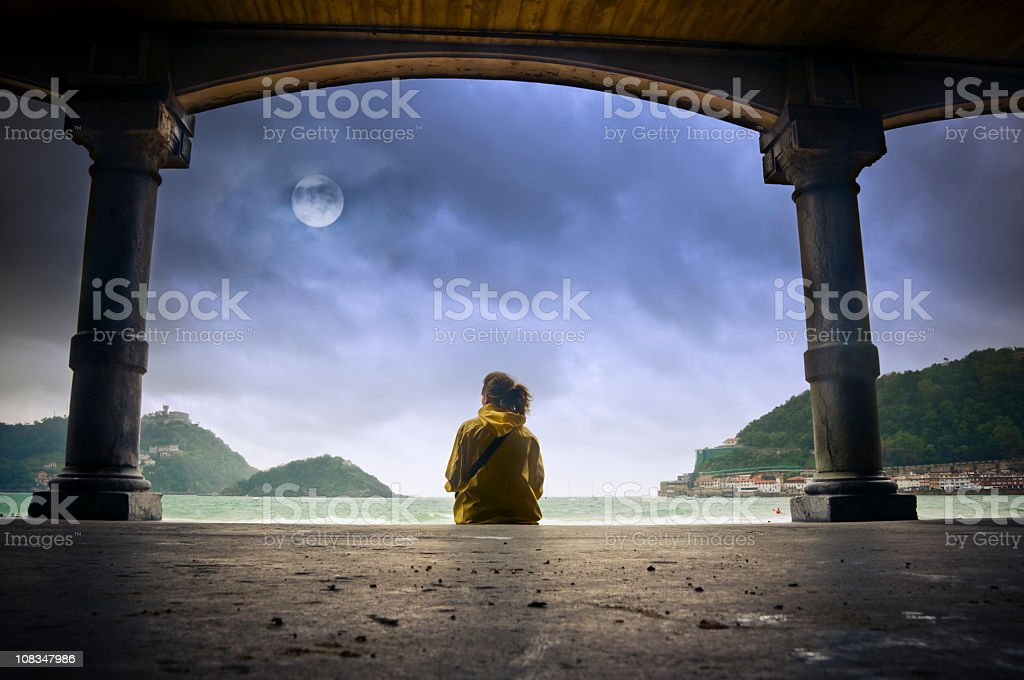 Young girl looking at the moon in Donostia stock photo