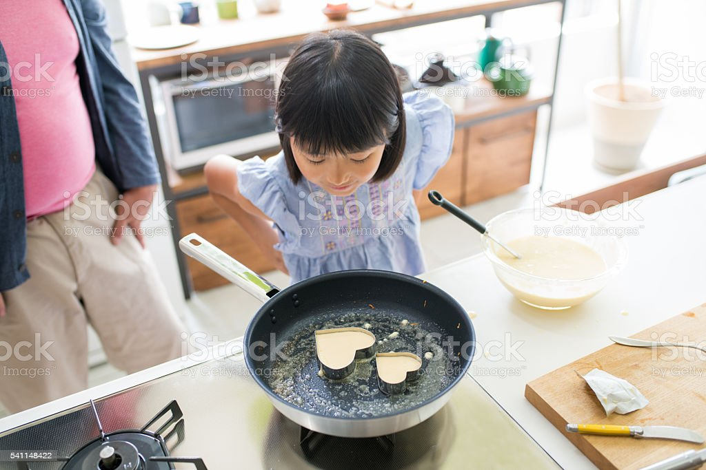 Young girl looking inquisitively into a frying pan stock photo