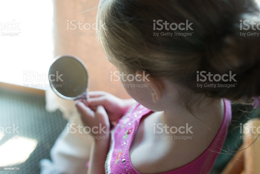Young girl looking into mirror stock photo