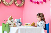 Young girl looking sad during tea party with stuffed animals