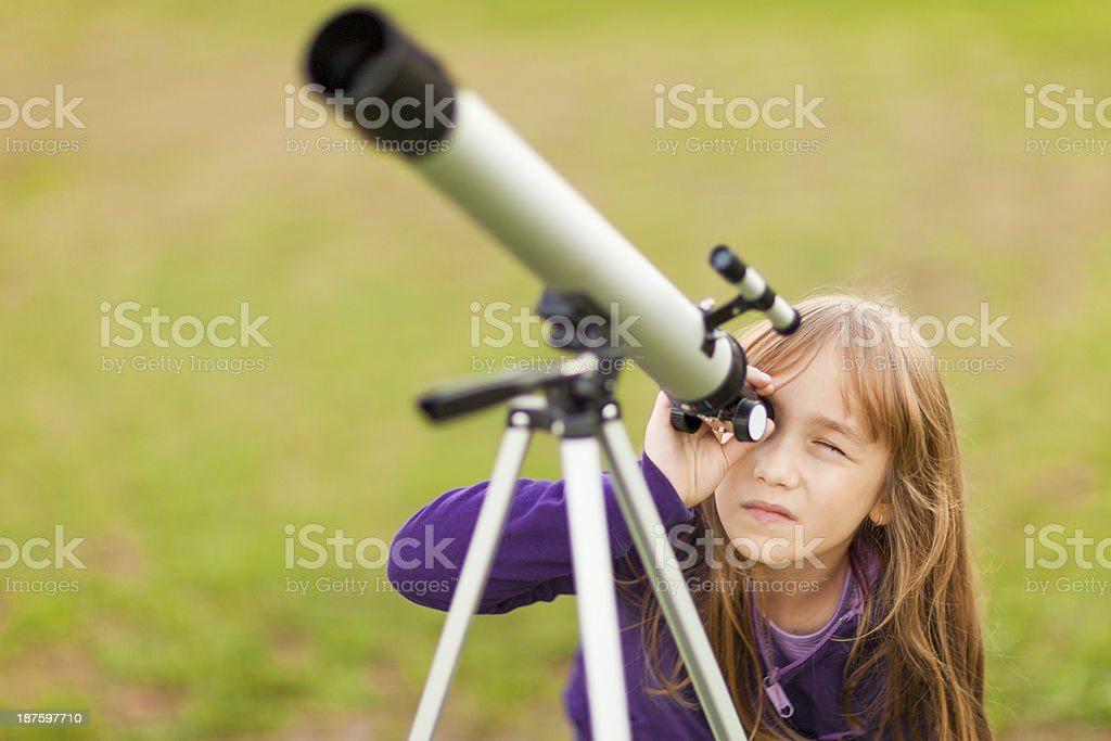 Young girl looking through telescope outside  stock photo
