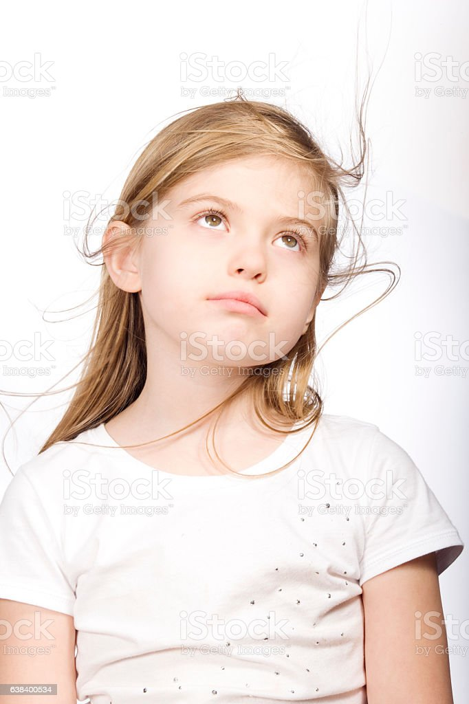 Young girl looking upward with hair blowing on white background stock photo