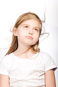 Young girl looking upward with hair blowing on white background