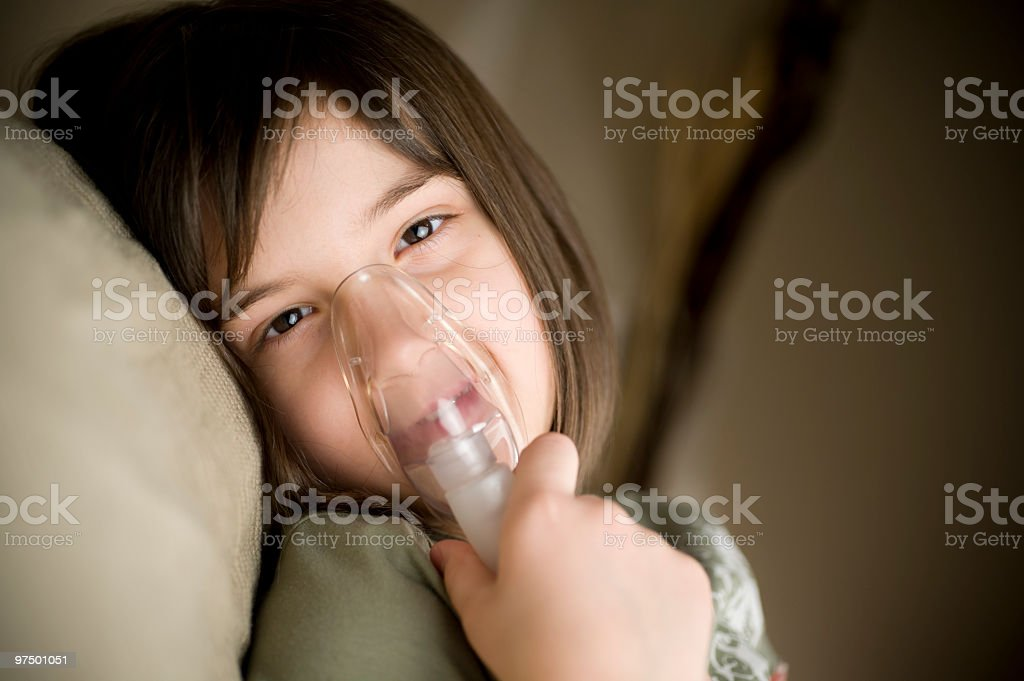 Young girl lying down using an inhaler device stock photo