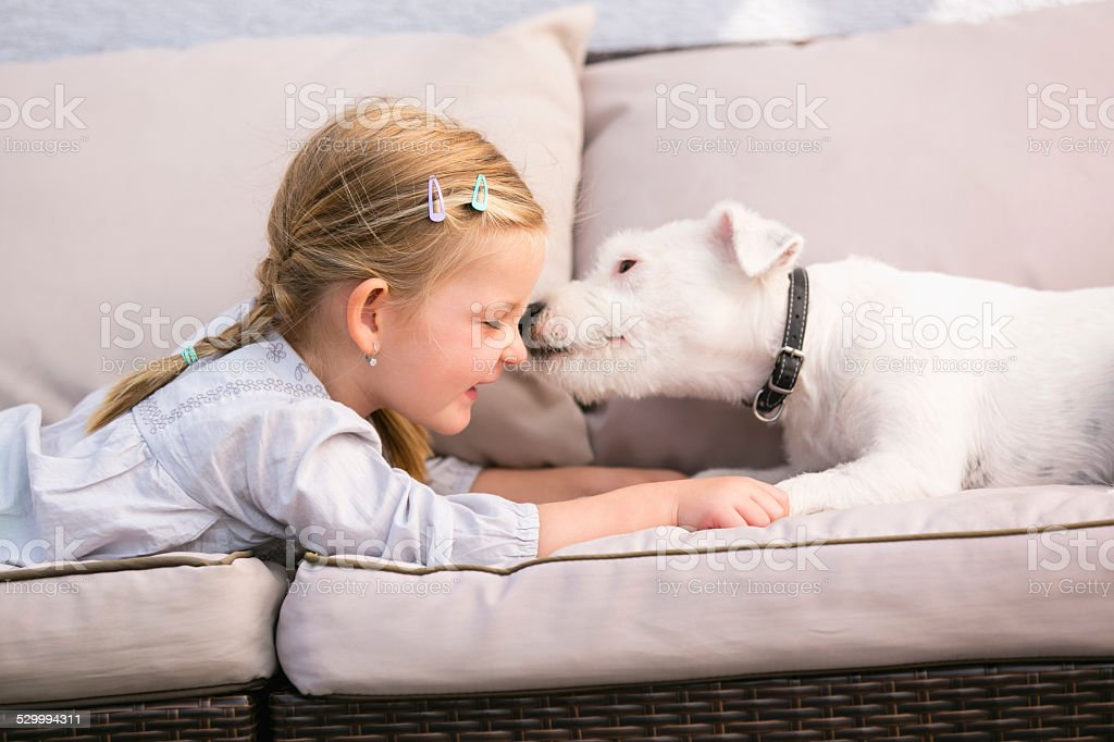 Young girl lying with pet dog on couch stock photo