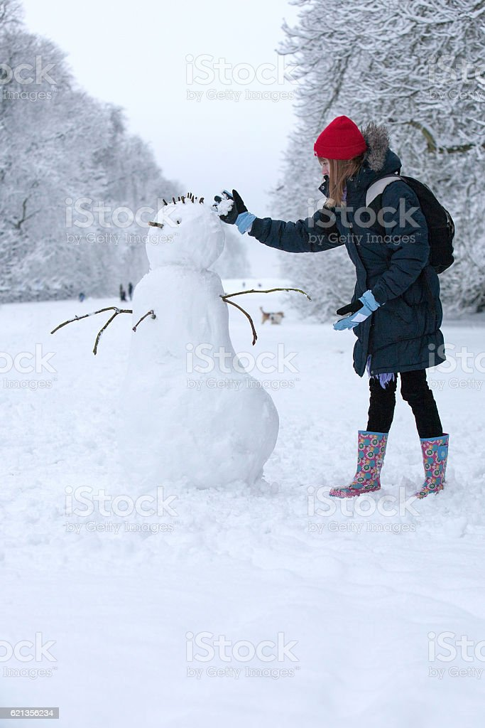 Young girl making a snowman in Cirencester park stock photo