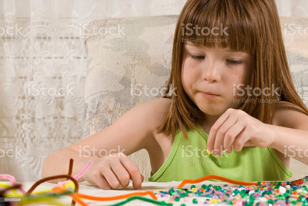 Young girl making bead bracelets stock photo