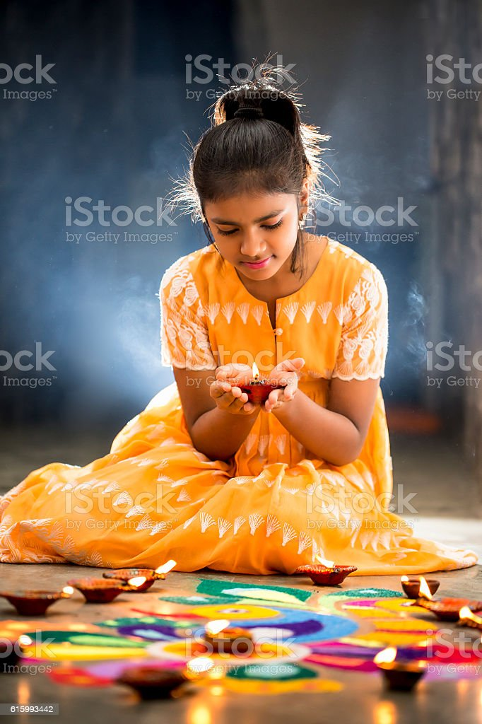 Young Girl making Rangoli, decorating with oil lamps for Diwali stock photo