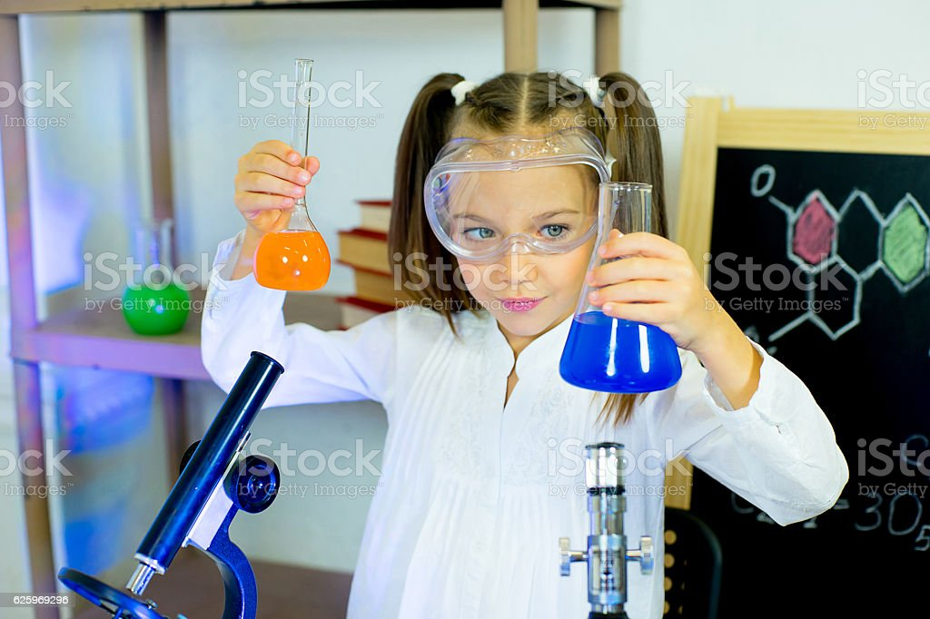 young girl making science experiments stock photo