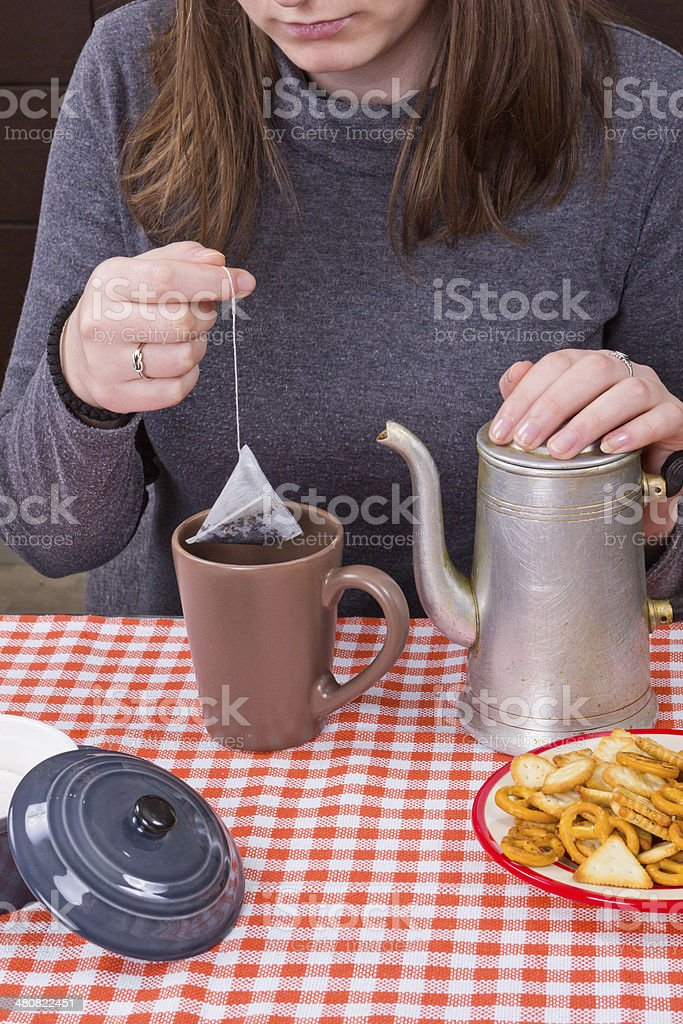 Young girl making tea at kitchen stock photo