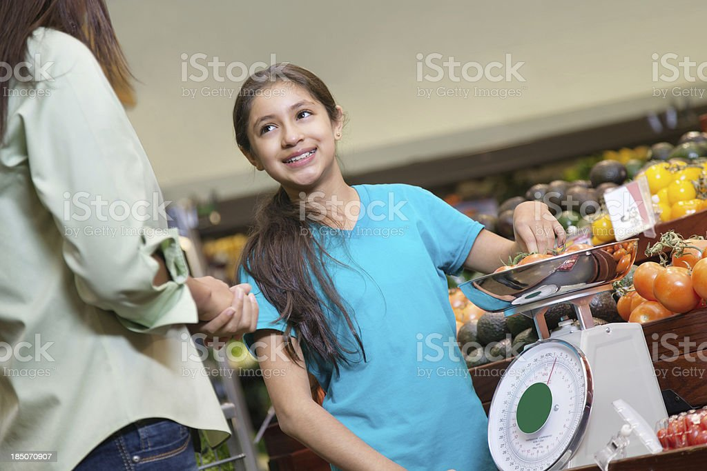 Young girl measuring tomatoes with mom at supermarket royalty-free stock photo