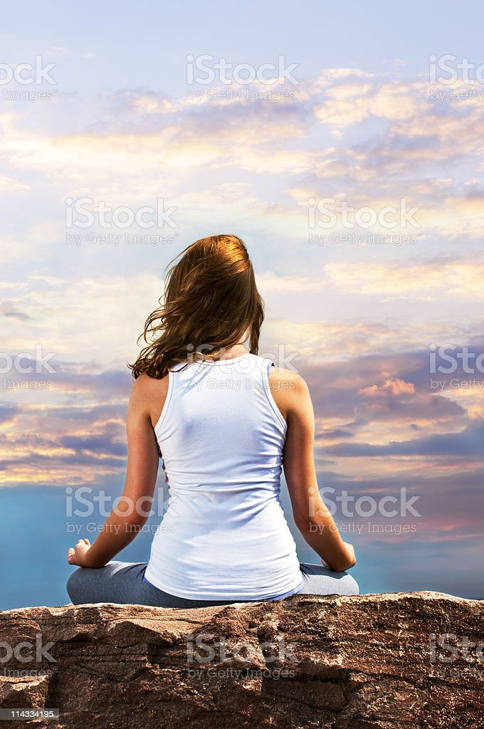 Young girl meditating at sunset royalty-free stock photo