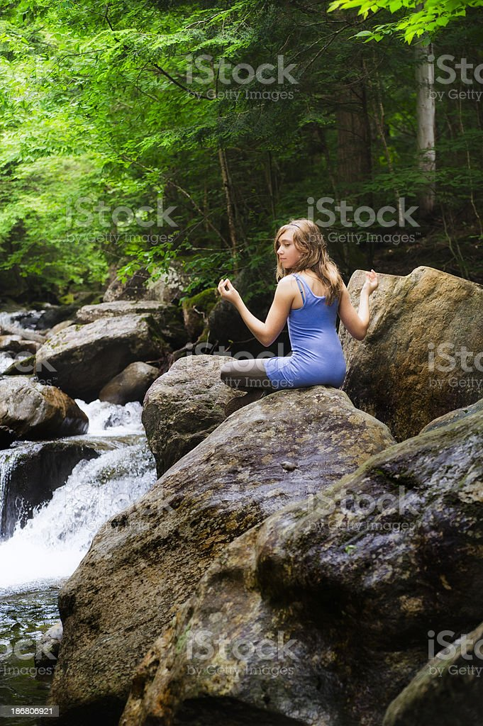 Young girl meditating in a waterfall. royalty-free stock photo