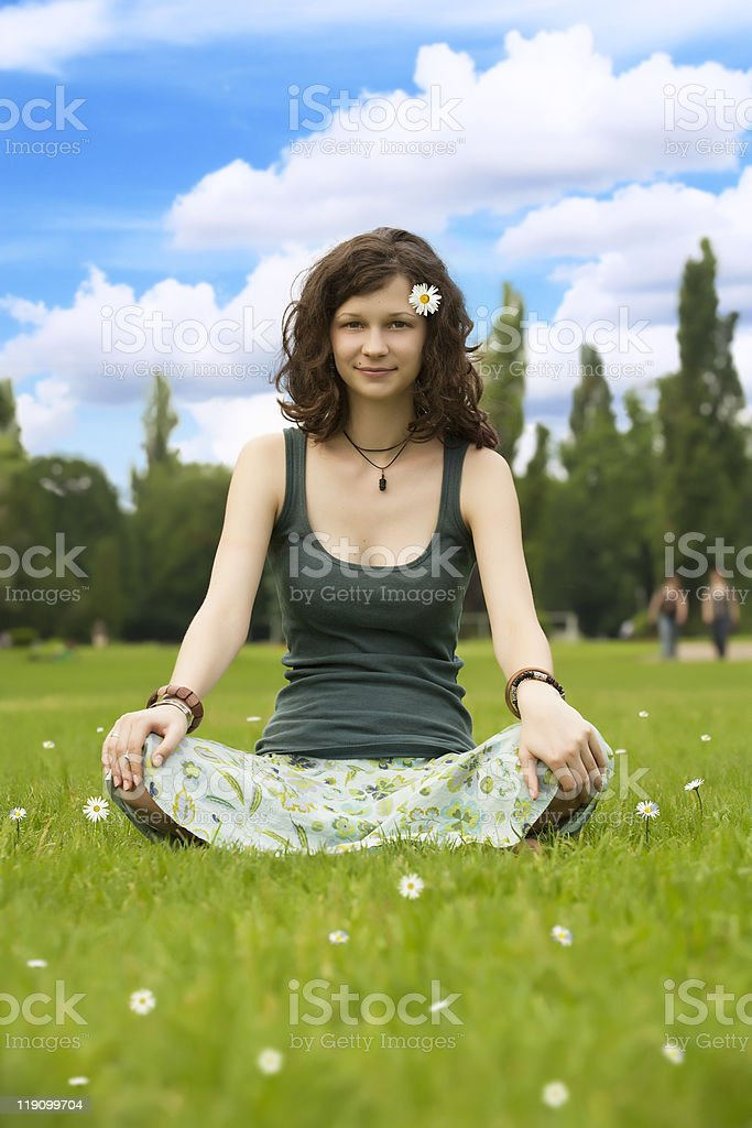 Young girl meditating under the clear sky stock photo