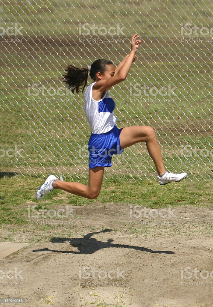 Young girl mid-air whilst attempting the long jump royalty-free stock photo