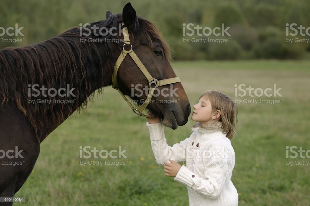 Young girl model wrenched his face to horse. Lifestyle portrait stock photo