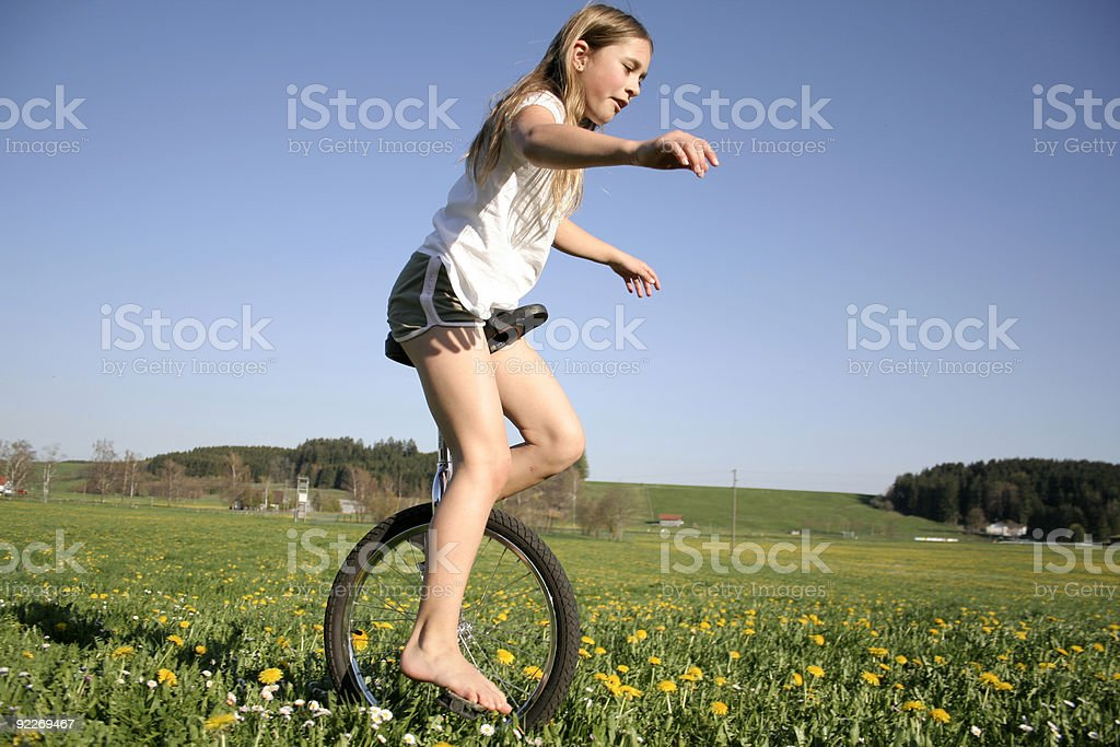 young girl monocycling in field stock photo