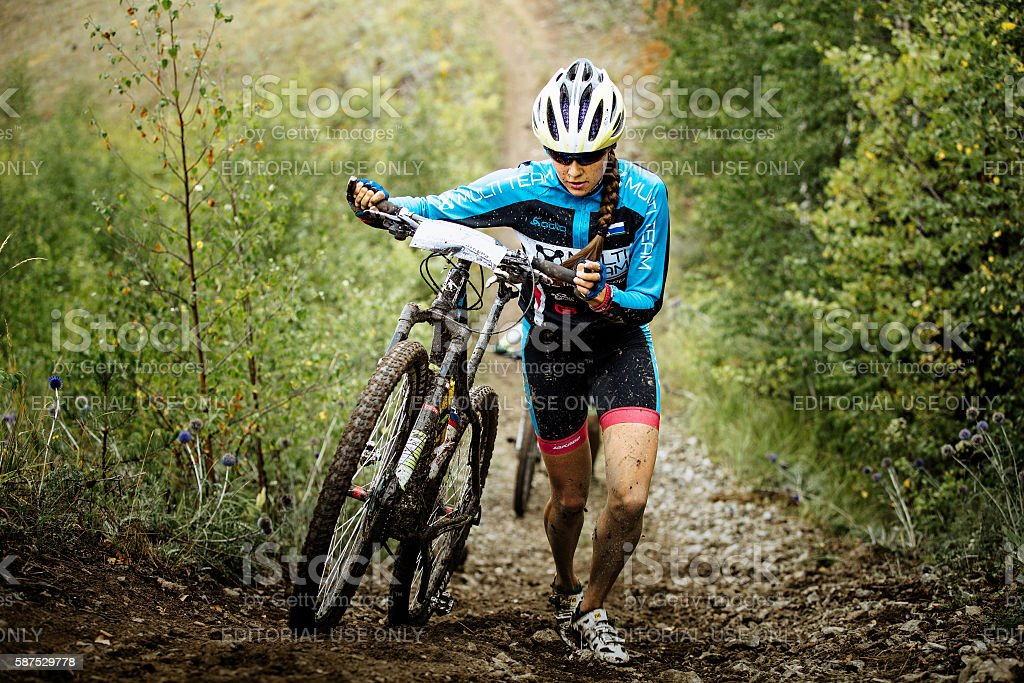 young girl mountainbiker climb mountain on foot with their bikes stock photo